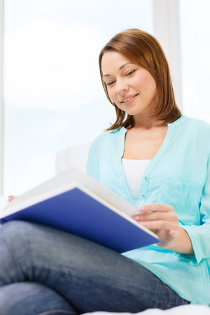 leasure and home concept - smiling woman reading book and sitting on couch at home Stock Photo - 25629605