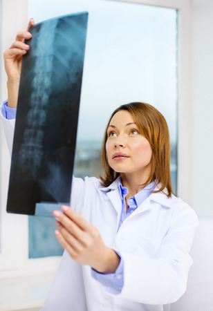 healthcare, medical and radiology concept - concentrated doctor looking at x-ray Stock Photo