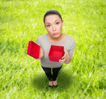 celebration, holidays and happiness concept - disappointed asian woman with empty red gift box photo