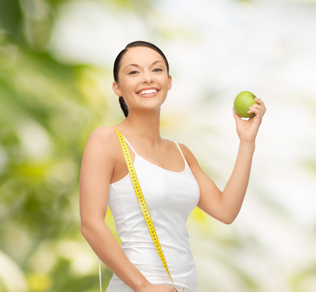 diet and health concept - beautiful sporty woman with apple and measuring tape