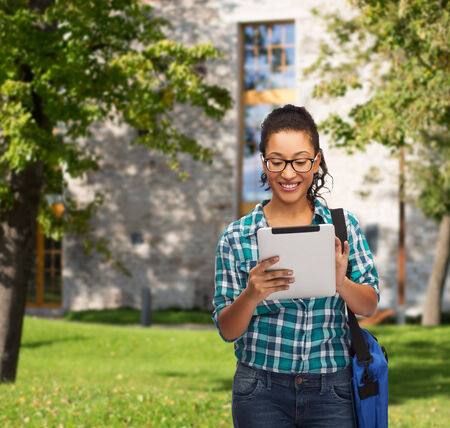 education, technology and people concept - smiling female african american student in eyeglasses with tablet pc and bag photo