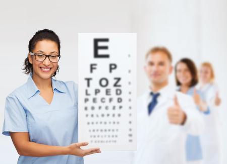 healthcare, vision and medicine concept - smiling female african american doctor or nurse in eyeglasses with small white blank board photo