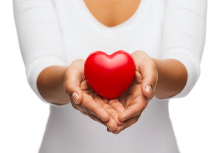 la gente, la relación y el concepto de amor - de cerca de la mujer ahuecadas manos que muestran el corazón rojo