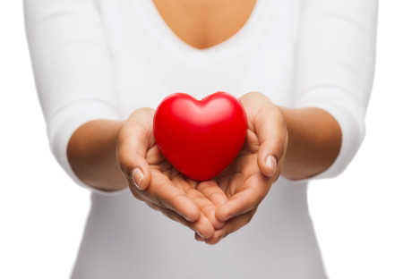 family health: people, relationship and love concept - close up of womans cupped hands showing red heart