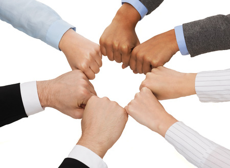 african solidarity: business and teamwork concept - closeup of businesspeople hands in fists in circle Stock Photo