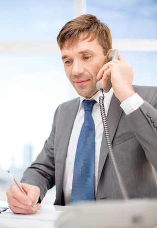 technology, business, communication and office concept - handsome businessman working with phone and documents photo