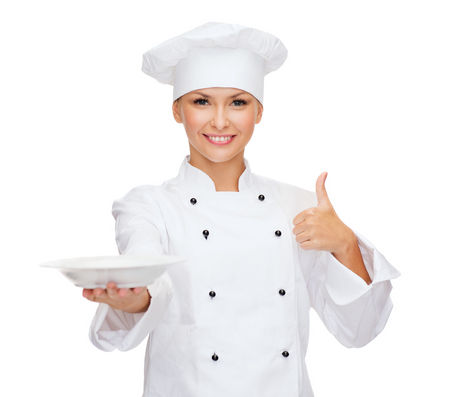 cooking and food concept - smiling female chef, cook or baker with empty plate showing thumbs up photo