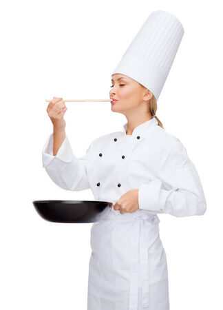 asian cook: cooking and food concept - smiling female chef with pan and spoon tasting food