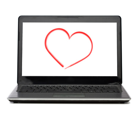 technology and advertisement concept - laptop computer with heart on white screen photo