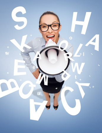 business and office concept - screaming businesswoman in eyeglasses with megaphone photo