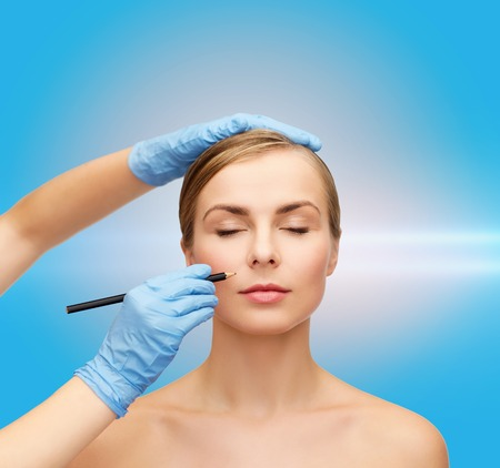 healthcare, beauty and medicine concept - beautiful woman face with closed eyes and beautician hands with pencil photo