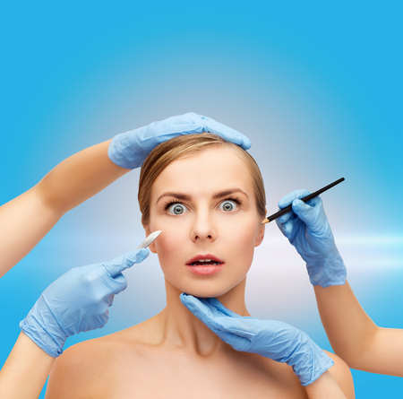 healthcare, beauty and medicine concept - beautiful woman face and beautician hands with pencil and scalpel photo