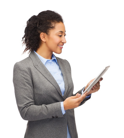 business, internet and technology concept - smiling african-american woman looking at tablet pc computer