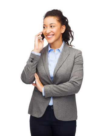 business, internet and technology concept - smiling african-american woman looking at smartphone photo