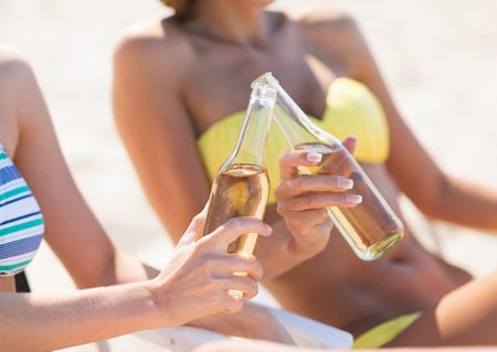 summer holidays and vacation - two girls in bikinis with drinks on the beach chairs photo