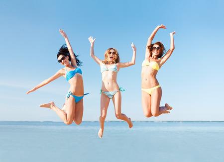 летние праздники и каникулы - девушки прыгает на пляже Фото со стока