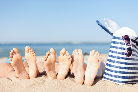 women feet: hats and summer concept - three women lying on the beach with straw hat, sunglasses and bag