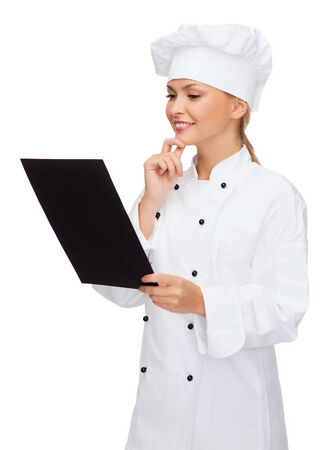 cooking, advertisement and food concept - smiling female chef, cook or baker with blank black menu paper photo