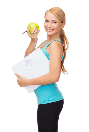 diet, sport and healthcare concept - beautiful sporty woman with scale and green apple Stock Photo