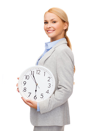 business and time concept - attractive businesswoman with wall clock photo