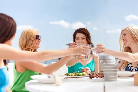bachelore party: vacaciones de verano y concepto de vacaciones - niñas, haciendo un brindis en la cafetería en la playa