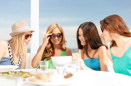 summer holidays, vacation, internet and technology concept - smiling girls looking at tablet pc in cafe photo