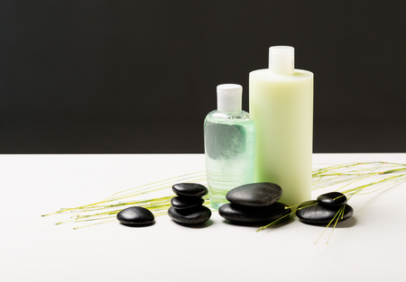 hair conditioner: spa, health and beauty concept - closeup of shampoo bottle, massage stones and green plant