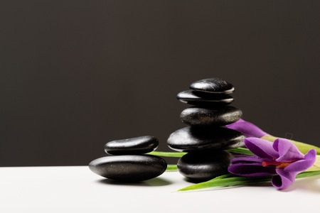 feng: spa, heath and beauty concept - massage stones with flowers on mat