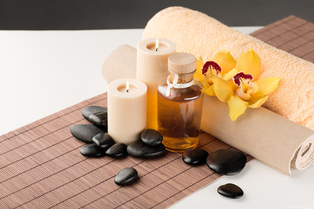 body oil: spa, health and beauty concept - closeup of essential oil, massage stones, candles and orchid flower Stock Photo