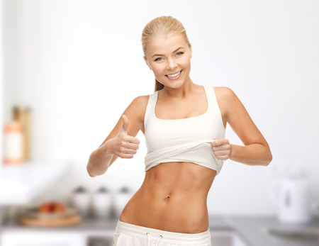 6 pack: diet and fitness concept - beautiful sporty woman showing thumbs up and her abs