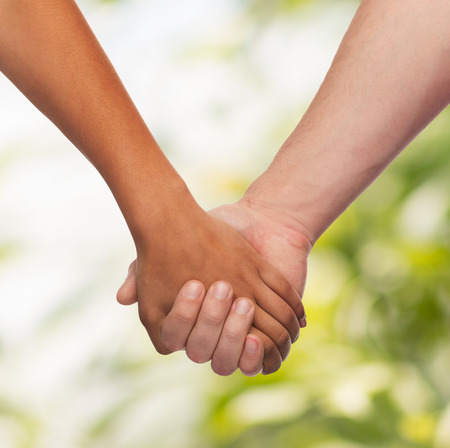 holding hands: love and relationships concept - closeup of woman and man holding hands