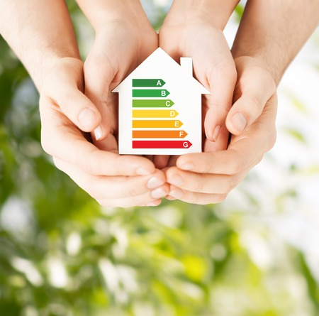 bio energy: energy saving, real estate and family home concept - closeup of couple hands holding white paper house with energy efficiency rating Stock Photo