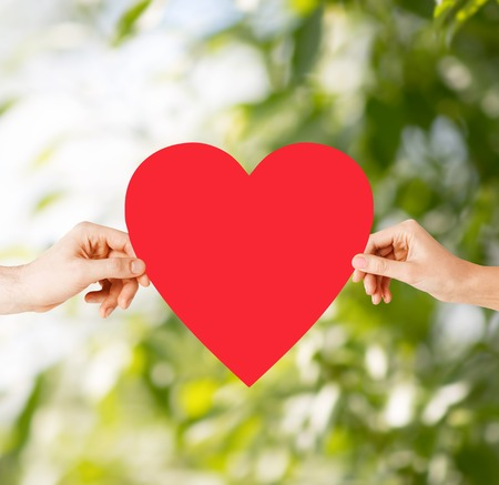 lovers holding hands: health, love and relationships concept - closeup of couple hands with big red heart