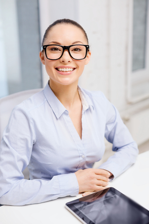 office, business, education, technology and internet concept - smiling businesswoman in eyeglasses with tablet pc in office photo