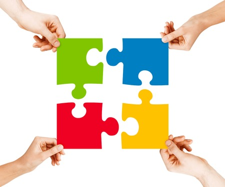 business, teamwork and collaboration concept - four hands connecting colorful puzzle pieces photo