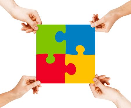 Negocio, trabajo en equipo y colaboración concepto - cuatro manos conectadas coloridas piezas del rompecabezas Foto de archivo - 25691306