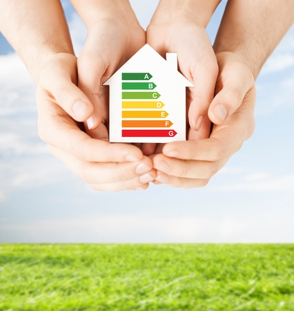 save the environment: energy saving, real estate and family home concept - closeup of couple hands holding white paper house with energy efficiency rating Stock Photo