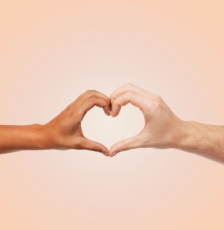 love and relationships concept - closeup of woman and man hands showing heart shape photo