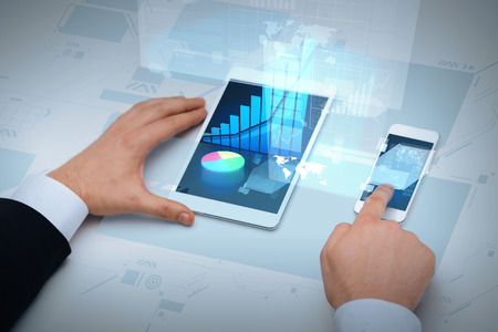 business, internet and technology concept - close up of businessman hands working with table pc and smartphone Imagens