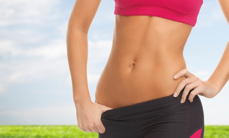 girl belly: diet and fitness concept - close up picture of woman trained abs