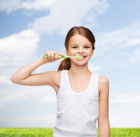 dental hygiene: shirt design, health, oral hygiene, dental concept - smiling teenage girl in blank white shirt brushing her teeth Stock Photo
