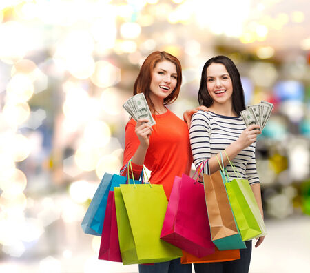 shopping, sale and gifts concept - two smiling teenage girls with shopping bags and cash money photo