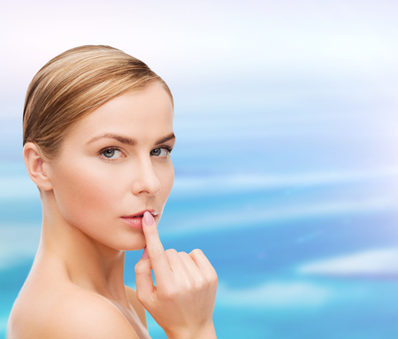 health and beauty concept - clean face of beautiful young woman pointing finger to her lips photo