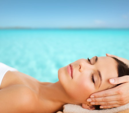 health resort treatment: spa, resort, beauty and health concept - beautiful woman in spa salon getting face treatment