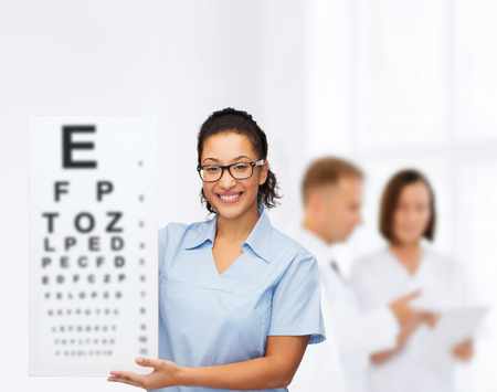 healthcare, advertisement and medicine concept - smiling female african american doctor or nurse in eyeglasses with small white blank board photo