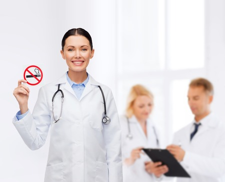 quitting: healthcare and medicine concept - smiling female doctor with stethoscope holding no smoking sign Stock Photo