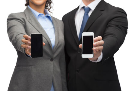 business, technology and internetconcept - businessman and businesswoman with blank black smartphone screens photo