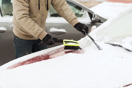 transportation, winter and vehicle concept - closeup of man cleaning snow from car windshield with brush photo