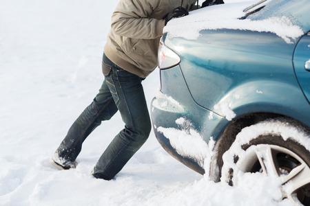 empujando: el transporte, el invierno y el concepto de vehículo - de cerca de un coche que empuja al hombre atascado en la nieve