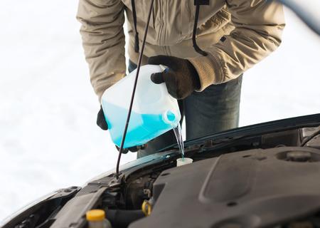 交通機関、冬、車両コンセプト - フロント ガラスの水タンクに不凍液を注ぐ男のクローズ アップ